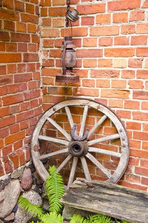 paraffine: Antieke houten wagen wiel met de binding van metaal en hoefijzer op het Kerosine paraffine roestige lamp Rode bakstenen muur Fern bladeren Stockfoto