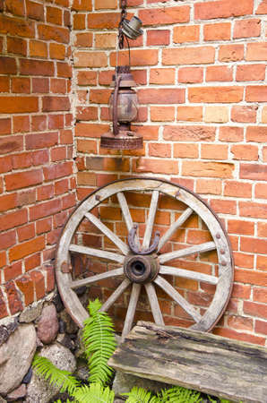 Antique wooden carriage wheel with binding of metal and horseshoe on it  Kerosine paraffin rusty lamp  Red brick wall  Fern leaves   photo