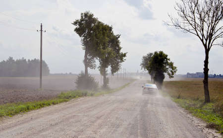Dusty rural gravel road between farm fields and the machine going. Stock Photo - 12567484