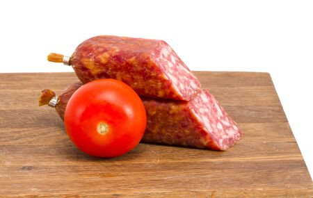 cut smoked sausage pieces and tomato on cutting board isolated on white background   photo