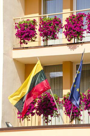 Lithuania and European Union flag hanging under building balcony with flowers.