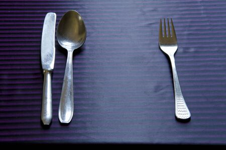 Vintage metal flatware tableware placed on the cloth by etiquette  Spoon, fork and knife   photo