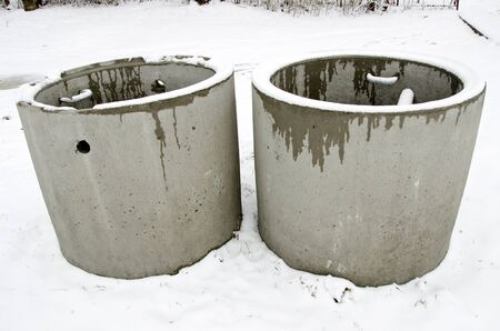 Concrete manholes with ladder protruding from ground in winter  Urban waste water treatment system   Stock Photo