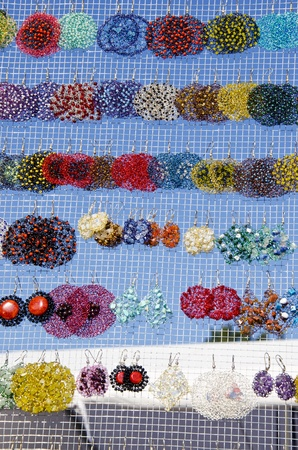 many colorful handmade earrings for sale at outside street market fair   photo