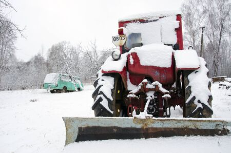 old russian soviet tractor covered with snow in winter. retro vintage machinery adapted to snow plowing.