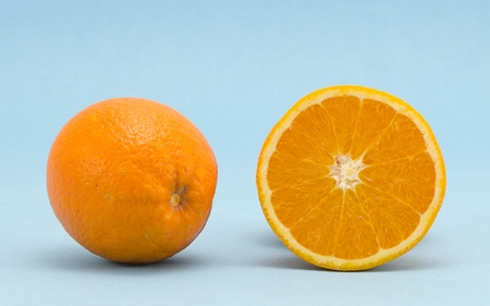 sectioned: Oranges fruits full and sectioned on blue background. Healthy organic nutrition food objects.