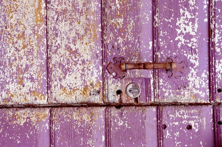 Background of an old painted, crumbled door. Handle on purple wooden planks.  photo