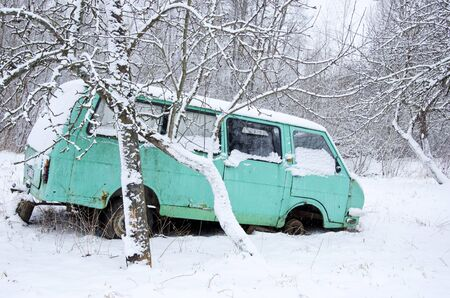 Old broken minibus covered with snow in winter garden near apple trees