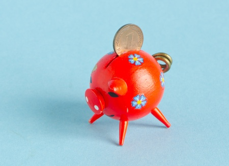 nestegg: Red piggybank on blue background  Saving money for black day in pig money-box  Nest-egg  Pfennig