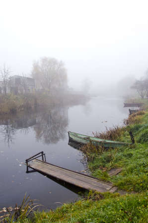 Wooden rowing boats and bridge standing on coast of river sunken in mysterious dence fog   photo