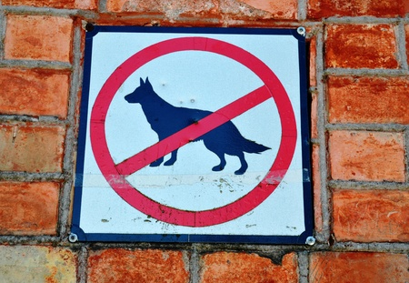 Sign prohibiting walk out dogs in park on red brick house wall   photo
