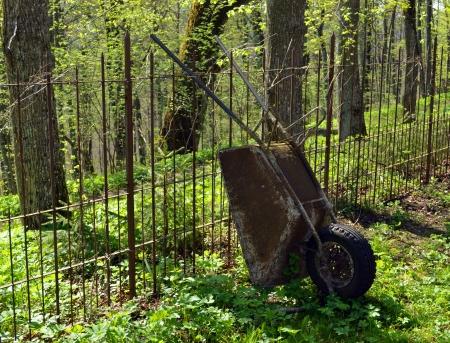 Old rusty village garden wheelbarrow rest near metal barbed fence  Tool for garden works