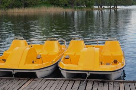 Yellow water bicycles locked at lake marina  Active recreation objects   Stock Photo