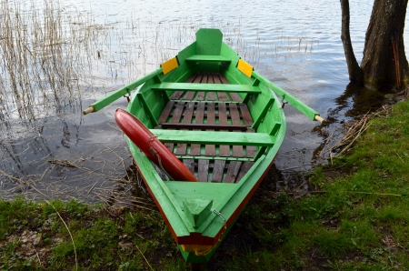Rowing wooden boat near lake shore and red life saver resque circle in it   photo
