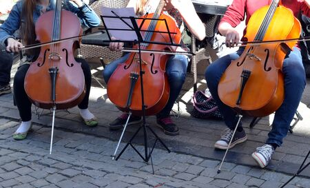 Young people playing cello violoncello bass-viol in street music day in Old Town street  Free event   photo