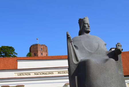 Gediminas castle on high hill, nacional museum of Lithuania and Mindaugas grand duke and first king of Lithuania sculpture on background of blue sky