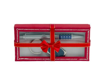 Pen and key ring packed in red gift box with ribbon isolated on white background   photo