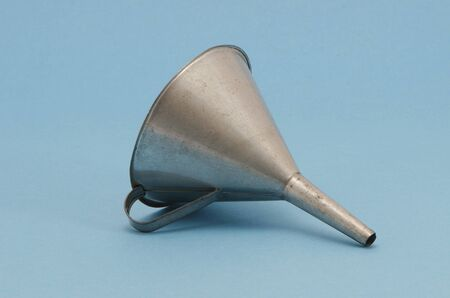 Ancient metal aluminum funnel on blue background.  photo