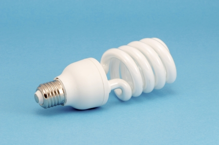 Novel fluorescent light bulb on blue background. New technology for less electricity energy consumption.  photo
