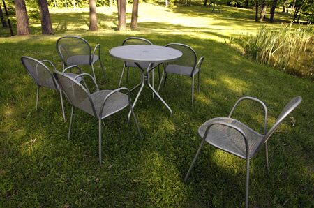 Chairs maid of metal near pond on meadow grass in garden   Stock Photo - 14303697