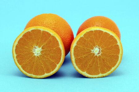 Oranges fruits full and sectioned on blue background  Healthy eating organic food items