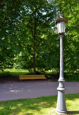 Vintage retro park lamp light pole and yellow wooden bench under trees for recreation