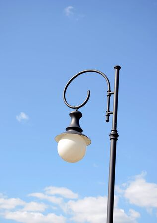 Park round lighting lamp on metal pole on background of blue cloudy sky   photo