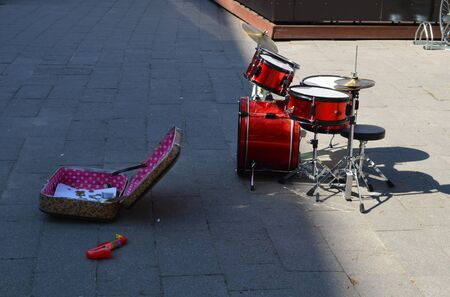 Empty place of children kid drum set and suitcase with money in it on street pavement  Street music day   photo