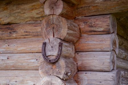Horseshoe hang on wooden log house corner  Sign symbol of luck   Stock Photo