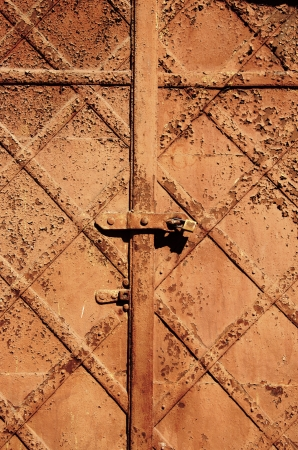 Ancient vintage retro rusty abandoned steel door background locked with small lock   photo