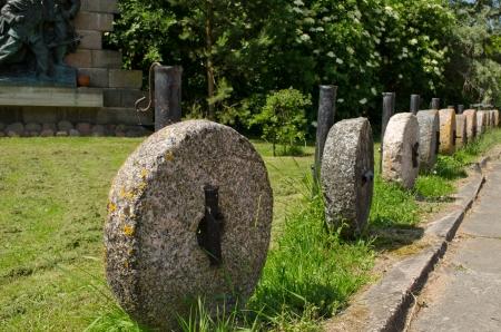 millstone: Retro rock millstones hanging on metal columns  Car parking decorations in park