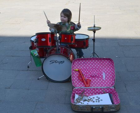 VILNIUS, LITHUANIA MAY 2012 Young kid child play with drums. Earn money in street music day.