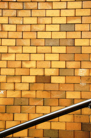 Background of yellow brick wall and steel stair railing   Stock Photo - 14536958
