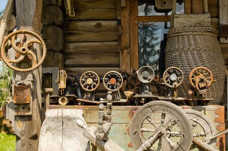 Old sewing and weaving machines equipment tools to the old rural log house  photo