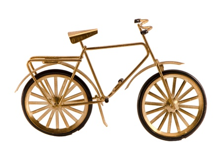 Small gold color toy bicycle isolated on white background   photo