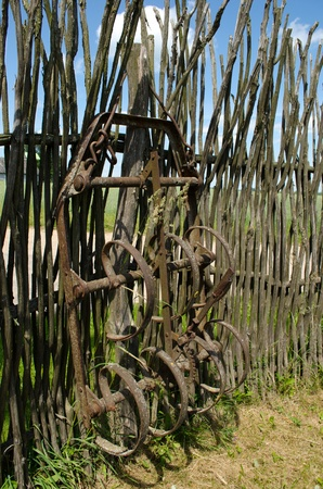 harrowing: Old corroded harrowing field the tool stand near handmade fence from tree branches.  Stock Photo