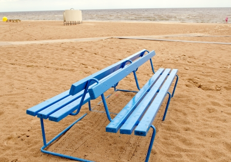 Blue bench on seaside sand after rain  Bathing box in beach   photo