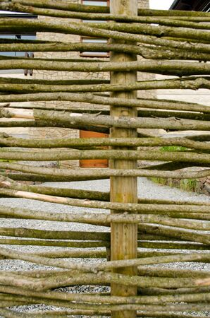 Background of fence made of weaven wooden branches and house yard Stock Photo - 14786943