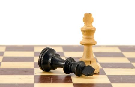 Nero si trovano nei pressi di re di scacchi vincitore bianco sulla scacchiera isolato su bianco
