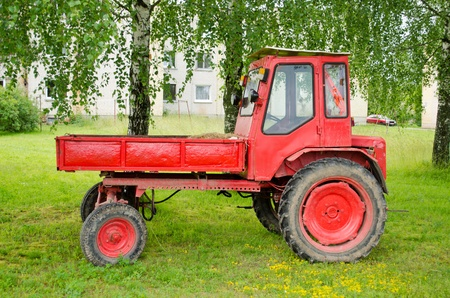 Retro red agricultural tractor with trailer near birch tree in small town   photo