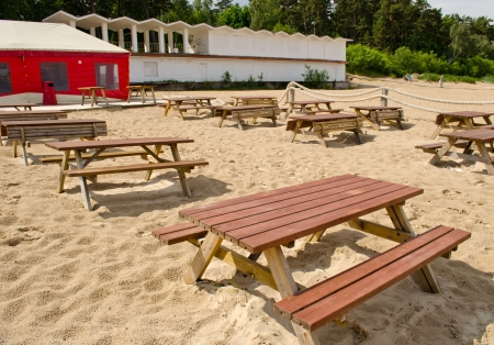 Wooden tables and benches surrounded by sea sand and huge cafe tent.  photo