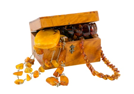Amber jewelry in vintage wooden box chest isolated on white background