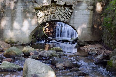 Retro architecture arch in wall and stream flowing from waterfall