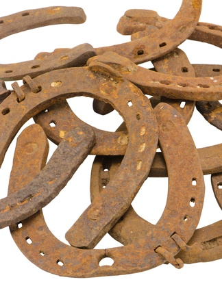 stack of old retro horse shoes isolated on white background   photo