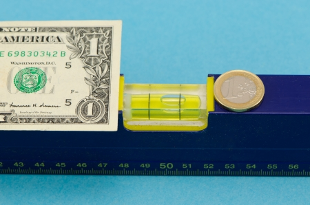 spirit level tool and usd dollar banknote and euro coin on blue background   Stock Photo