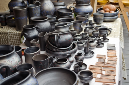 various handmade dark black clay pottery craft dishes pots cups jugs sell in outdoor street fair market  photo