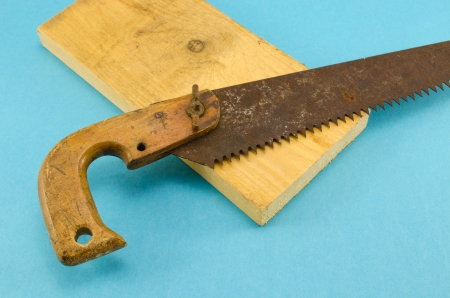 retro rusty crosscut hand saw handsaw tool and part of wooden board on blue background  Stock Photo - 16158075