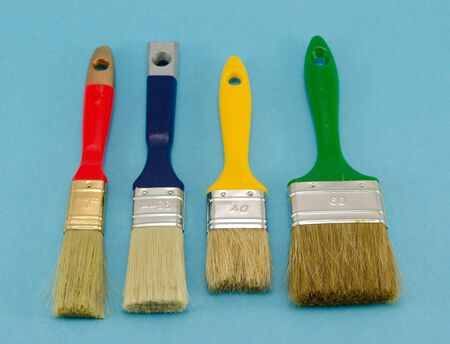 different colors and size paint brushes on blue background   photo