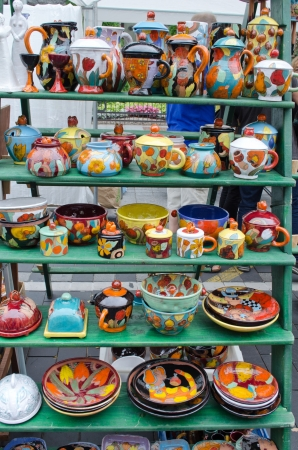 various colorful handmade clay pottery craft dishes pots cups jugs and other sell in outdoor street fair market  photo