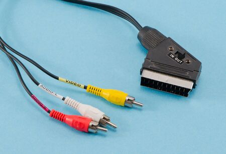 scart: tv scart cable connector and audio video colorful tulip wires plugs on blue background